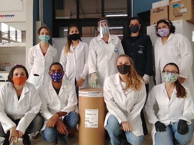chemists posing with masks in front of a barrel